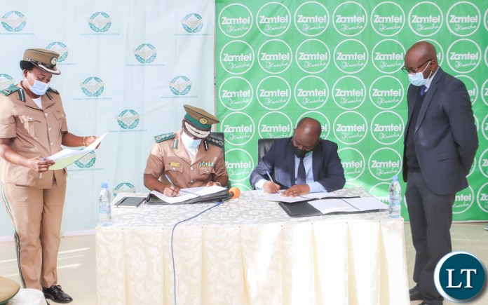 Zambia Correctional Service Commissioner General Dr Chisela Chileshe and Zamtel CEO Mr Sydney Mupeta signing an MoU to digitalise operations of the Correctional Service
