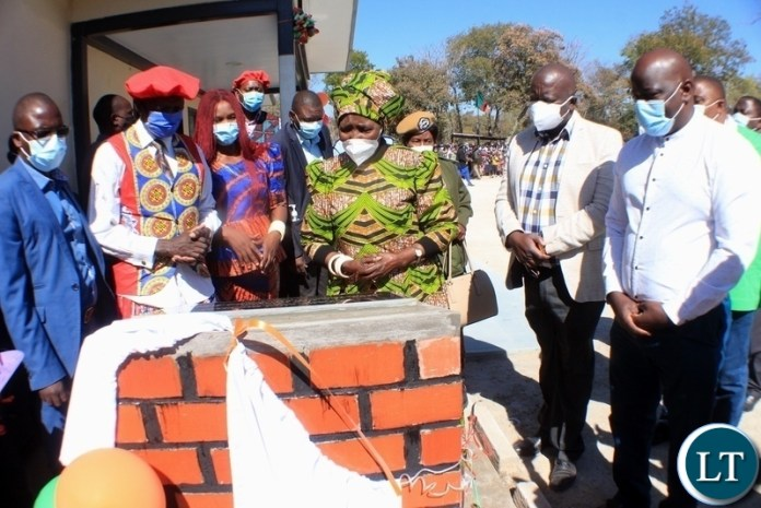 Vice President Inonge Wina (c) reads the message on the plaque as Western Province Health Director Dr. Francis Lyiwalii (r) observes during the commissioning of Lutaba Mini Hospital in Mwandi District