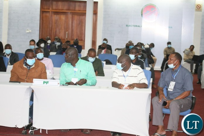 PF party members follow proceeding during the Electoral Commission of Zambia briefing at the National Results Center Mulungushi in  Lusak