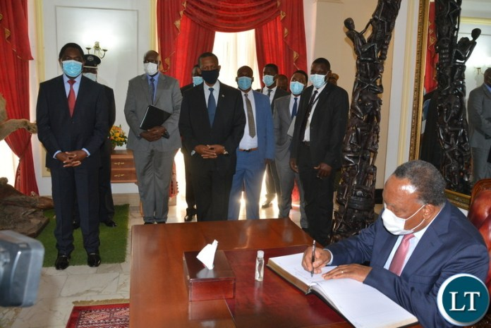 Former President of South Africa, Kgalema Motlanthe signing the Visitors' book at state house as President Hakainde Hichilema looks on.