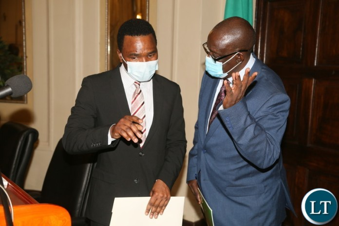 Special Assistant to the President for Press and Public Relations Anthony Bwalya confers with Permanent Secretary State House Dr. Oliver Kalabo during press briefing at State House