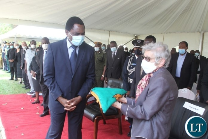 PRESIDENT Hakainde Hichilema confers with a Widow, Sara Zukas after presentation of a National flag at the burial and Funeral Service of Late former Cabinet Minister Hon. Simon Ber Zukas in Lusaka.