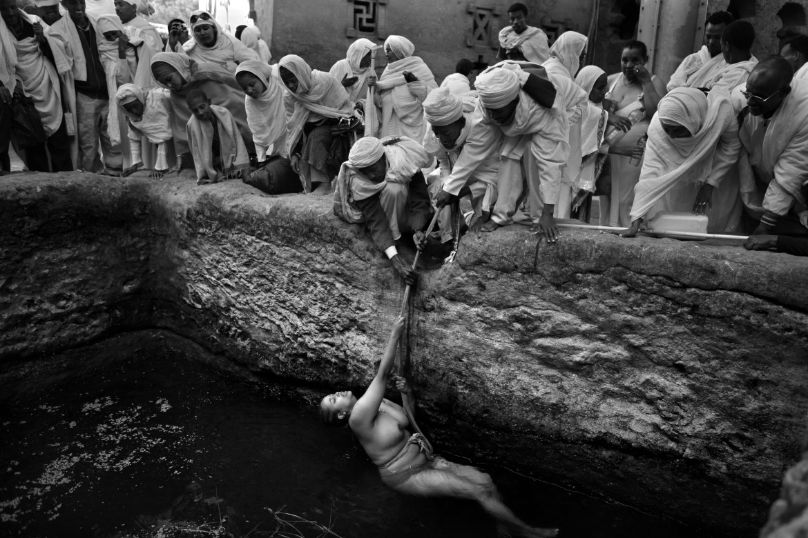 Pilgrims gather to watch as an infertile worshipper is lowered into a baptism pool with a rope held by priests; according to local faith the holy water has fertility powers that will allow her to conceive.  Every year, just before Christmas day (Julian calendar) thousands of pious Christian orthodox worshippers make pilgrimage to Lalibela, a small town in Ethiopia's highlands, known as Jerusalem of Africa or Black Jerusalem. Lalibela is famous for its 13th century monolithic churches, carved out of the living rock and one of the world's great wonders.