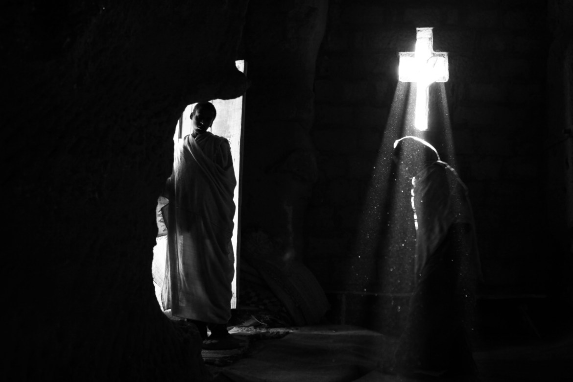 A ray of light penetrates into the church from a cross shaped window as a pilgrim walks by. Every year, just before Christmas day (Julian calendar) thousands of pious Christian orthodox worshippers make pilgrimage to Lalibela, a small town in Ethiopia's highlands, known as Jerusalem of Africa or Black Jerusalem. Lalibela is famous for its 13th century monolithic churches, carved out of the living rock and one of the world's great wonders.