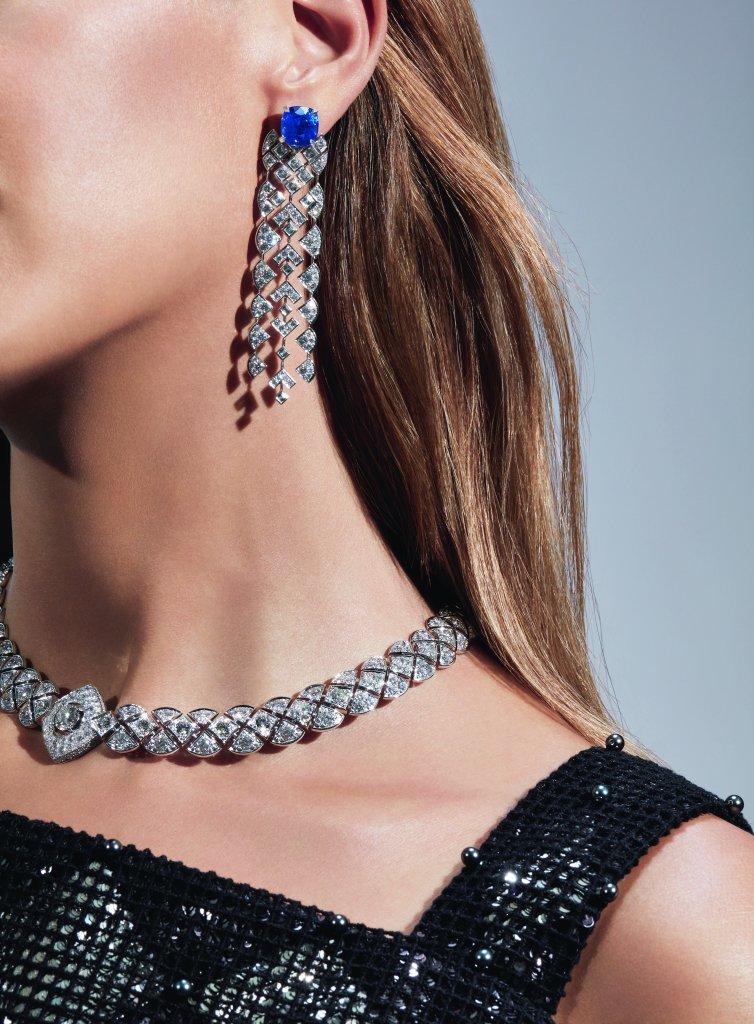 """Collier """"Signature Ultime"""" en or blanc 18K serti d'un diamant taille brillant de 1,5 carat et de 364 diamants taille brillant pour un poids total de 25,42 carats. Boucles d'oreilles """"Signature de Saphir"""" en or blanc 18K serti de 2 saphirs taille coussin pour un poids total de 12,8 carats, 26 diamants taille carré pour un poids total de 2 carats, 158 diamants taille brillant pour un poids total de 4,5 carats et 2 diamants taille triangle. Photo par CHANEL Joaillerie"""