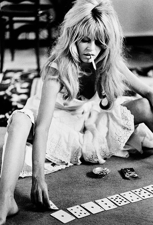 French actress Brigitee Bardot plays cards on set of the comedy-adventure film 'Viva Maria', 1965.