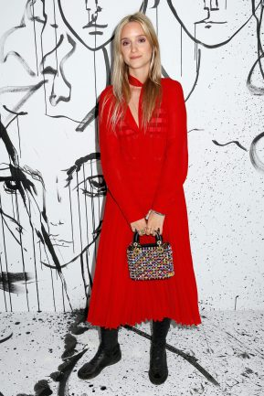 Charlotte Groeneveld portait une robe en crêpe de soie plissée rouge Dior. Elle portait également des bottes Dior et un sac « Lady Dior ».