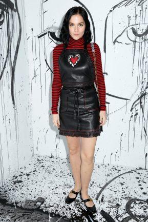 Leigh Lezark portait une robe en cuir noir Dior sur un pull col roulé à rayures noires et rouges Dior. Elle portait également des souliers « Baby-D » Dior et un sac Dior.