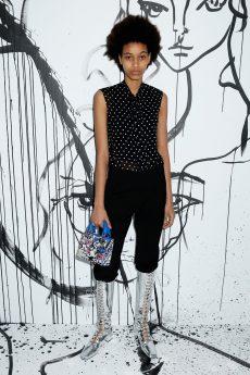 Manuela Sanchez portait une blouse en soie noire à pois blancs Dior sur un pantalon en laine noire Dior. Elle portait également des bottines « Naughtily D » Dior et un mini sac « Lady Dior ».