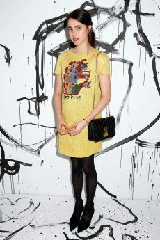 Margaret Qualley portait une robe à sequins jaunes et broderie « Positive » Dior. Elle portait également des bottines Dior et un sac Dior « Addict ».