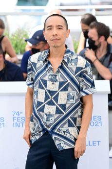APICHATPONG WEERASETHAKUL IS DRESSED BY DIOR HE WORE A NAVY SILK SHORT SLEEVE SHIRT WITH 'DIOR AND KENNY SCHARF' PRINT AND NAVY WOOL PANTS.