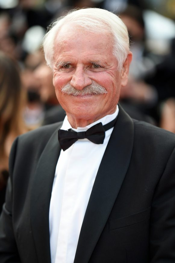 YANN ARTHUS BERTRAND IS DRESSED BY DIOR HE WORE A BLACK MOHAIR WOOL SHAWL COLLAR TUXEDO, WHITE COTTON WING-TIP COLLAR SHIRT WITH PLASTRON PIQUÉ AND A BLACK SILK BOW-TIE.