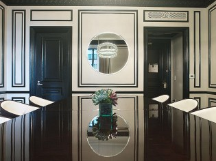 The dining room features an expansive media wall including a large TV as well as four Breitling clocks, Bentley's long-term partner, marking the time in New York, Riyadh, London and Moscow. The dining table uses Bentley's smoked fiddle-back eucalyptus veneer offset with metal engine-spin place settings. Bold, black trim is set against cream walls with artwork that displays the heritage of the Bentley brand: images taken from historic moments from the brand's founding to the present day.