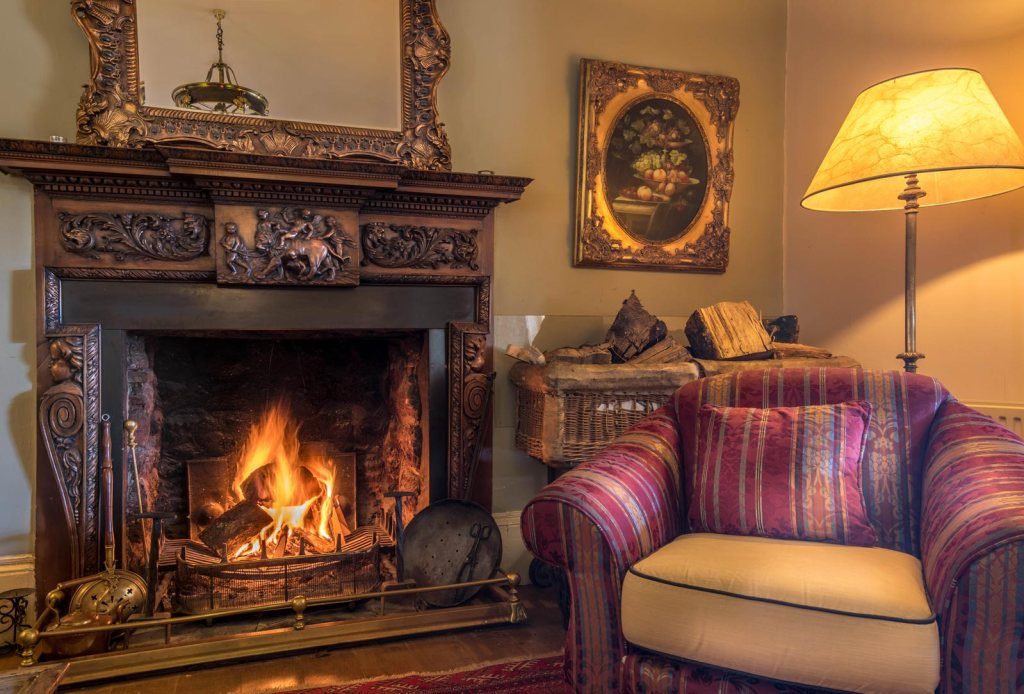 A roaring fireplace in the guests lounge at Orestone Manor in Devon