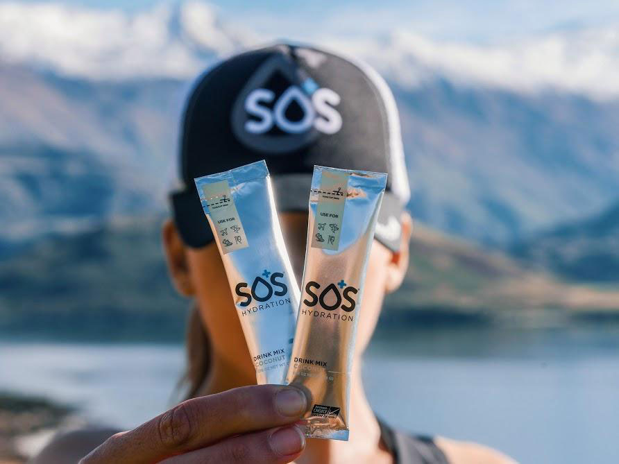 Athlete holding up packets of SOS Hydration