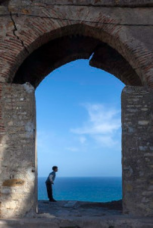 travel photography - A boy frolicks in an ancient archway of an old fortress wall; Tangier, Morocco