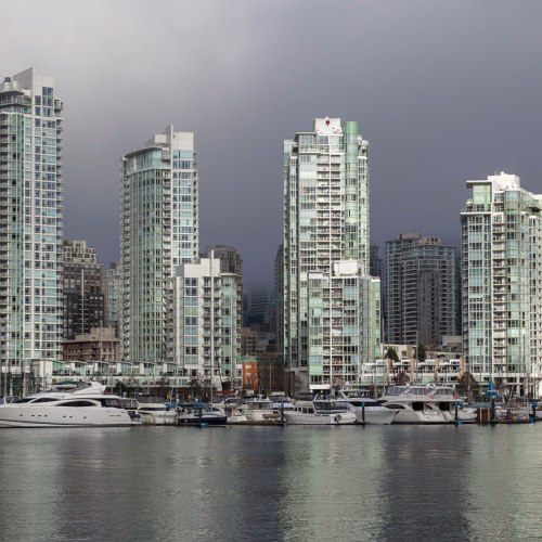 Sun shines through broken clouds and illuminates the Vancouver's Yaletown marina. Vancouver, Canada.