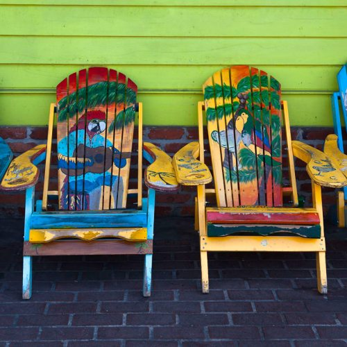 Colourful folk art chairs in front of Key West store, Florida. USA