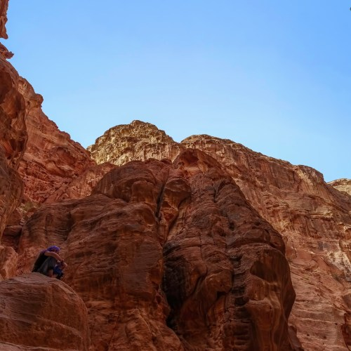 A man sits above the ruins in Nabatean city of Petra in Jordan