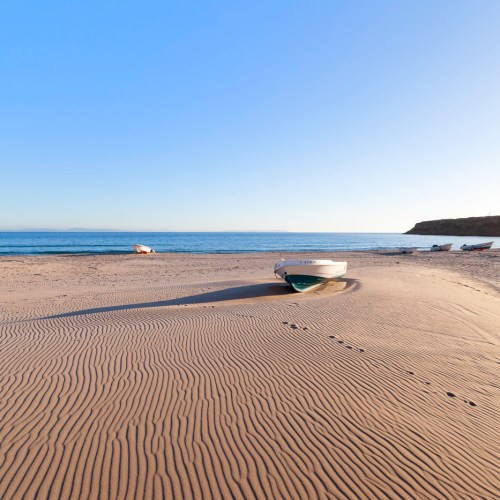 Small boat resting on patterned beach at coastal village of Bolonia. Tarifa, Spain.