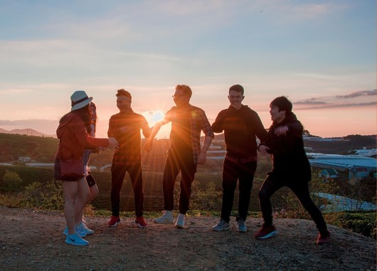 A group of teens or high schoolers at sunset.