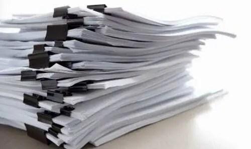 Documentação empilhada separada com clips. Papéis brancos com clips preto segurando blocos de folhas em cima de mesa.