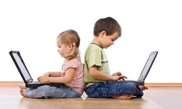 Duas crianças, uma menina e um menino, usando laptop. Crianças de costas umas para a outra, deixando de interagirem entre sim e interagindo pelo computador.