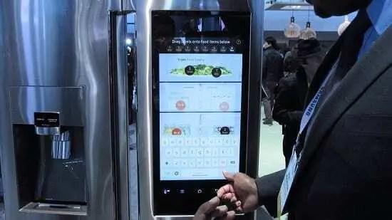 Painel de geladeira moderna ligado com pessoa na frente apontado para o mesmo.