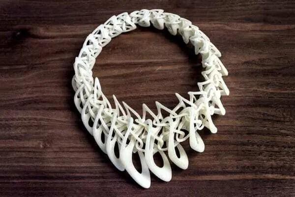 Colar impresso em 3D com detalhes menores na região da nuca e maiores na região do pescoço. Modelo na cor branca. Continue lendo nosso post!!