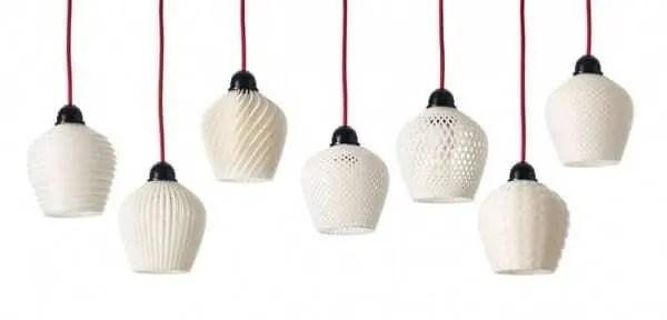 Luminárias vazadas na cor branca impressas em 3D penduradas por fio vermelho em um fundo branco.