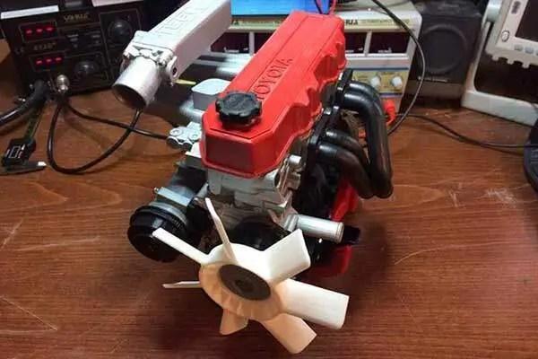 Motor antigo ta Toyota com detalhe vermelho e hélice impressa em impressora 3D. Conjunto do motor na cor preta.