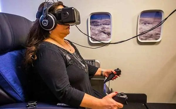 Mulher usando óculos de realidade aumentada fazendo tratamento em ambiente parecido com interior de avião.