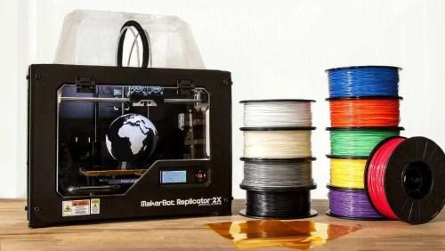 Rolos para serem usado em impressora 3D amontuados, um em cima do outro com cores diferentes (Branca, bege, cinza, preta, azul. vermelho, verde, amarelo e roxo) e impressora Makerbot Mini ao lado, com o globo terrestre impresso dentro.