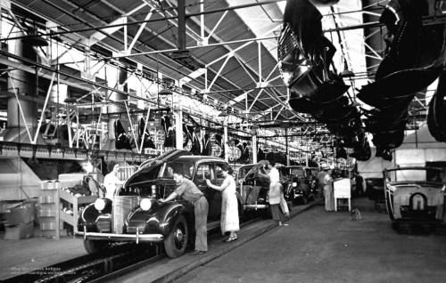 Operários trabalhando em linha de produção de fábrica automotiva. Mulheres e homens trabalhando na funilaria e motor dos carros.
