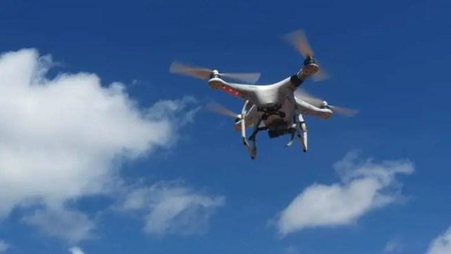 Drone sobrevoando cidade. Céu azul e nuvens no céu.