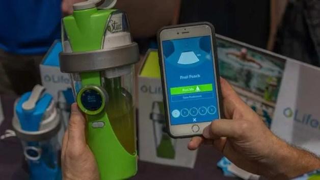 Homem segurando garrafa LifeFuels com líquido verde dentro e com a outra mão, utilizando função do Aplicativo da marca durante a CES 2016