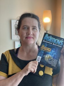 """Head and shoulders portrait of L.X. Beckett wearing a yellow tunic, holding the July/August 2021 issue of Asimov's Science Fiction, containing their story """"The hazmat sisters"""""""
