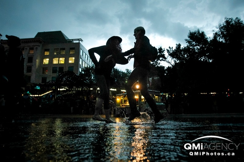 Sisters Haley and Katie Herrington dance under rainy skies at Olympic Plaza during the Sled Island Music and Arts Festival in Calgary, Alta., on Friday, June 20, 2014. The five-day festival takes place at many venues around town. Lyle Aspinall/Calgary Sun/QMI Agency