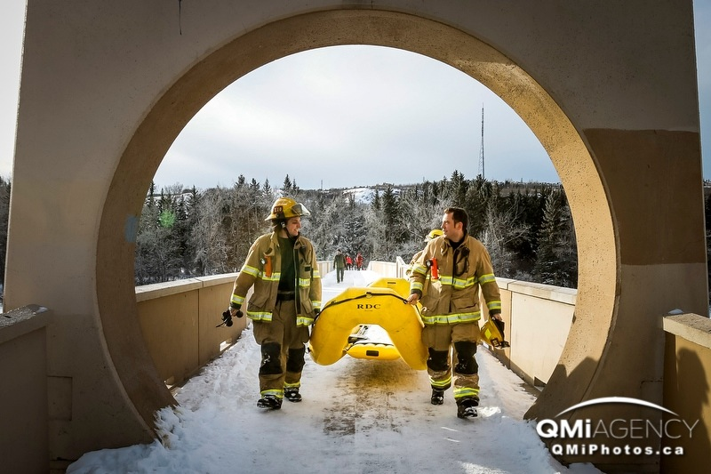 Firefighters carry a dinghy through an archway at Edworthy Park in Calgary, Alta., on Wednesday January 8, 2014. Firemen were initially trying to get the dogs out of the Bow River, but the dogs saved themselves and then scampered away down the shoreline; it's not clear why they were loose or to whom they belonged.