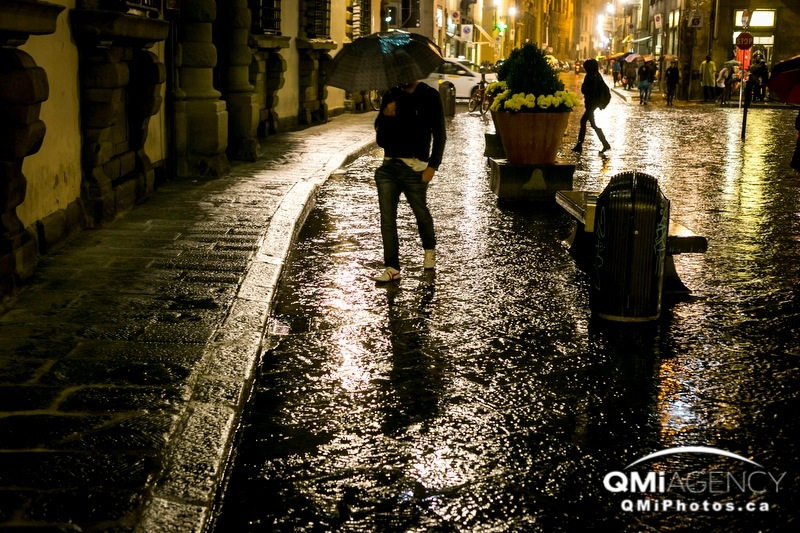 A man walks the wet streets of Florence, Italy, during a rainstorm on Monday, Nov. 4, 2013. Italy was entering its low season for tourism.