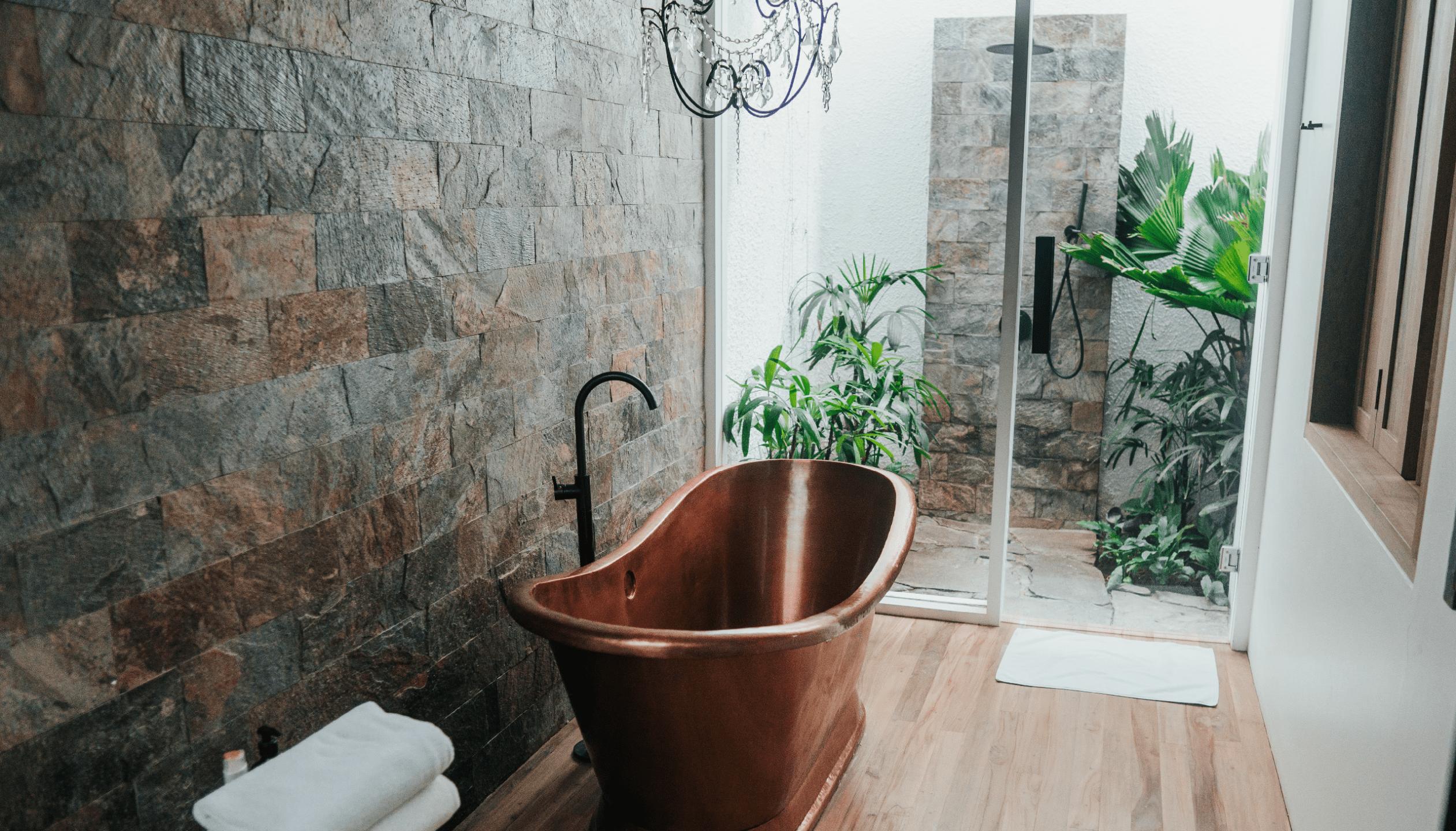 A copper freestanding bath tub in front of the patio door