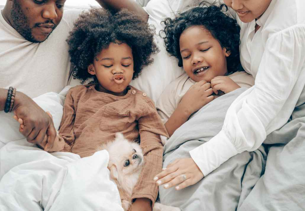 happy ethnic family resting in bed with little dog