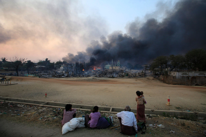 Smoke rises as people look on in Meikhtila, March 21, 2013. The central Myanmar town declared a curfew for a second night on Thursday after clashes killed 10 people, including a Buddhist monk, and injured at least 20, authorities said. Riots erupted in Meikhtila, 540 km (336 miles) north of Yangon, on Wednesday after an argument between a Buddhist couple and the Muslim owners of a gold shop escalated. REUTERS/Soe Zeya Tun (MYANMAR - Tags: CIVIL UNREST RELIGION) - RTR3F9XV