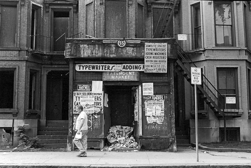 Dirty Old Boston - A man walks with a bag along the street in the South End, 1965