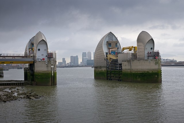 The skyscrapers of Canary Wharf glimpsed through the sleepingmaw of the mighty barrier. Photo George James.