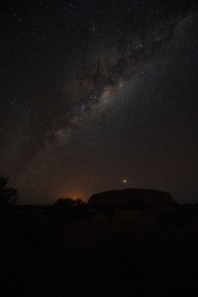 Uluru silhouetted against the Milky Way; the glow is the nearby Mutitjulu community, Canon 5D III and 16-35mm lens