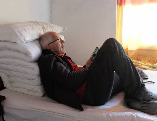 Trek colleague Tony quietly reading in the late afternoon light in the guesthouse. Every bed provides two substantial quilt blankets, really useful up there on a cold night in a basic room with no heating.