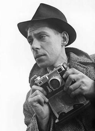 "Bert Hardy as a young photographer in 1941. Image courtesy of the Science Museum Group and Wikimedia Commons. Bert had put on a bit of weight when I met him forty years later, and was a big, jovial, red-nosed man, who took up farming after retiring from Picture Post. He'd taken the big billboard photos for the 'Strand cigarettes' ad campaign with his tiny coat-pocket Leica (he switched back and forth between Leica and this photo's Contax) but that campaign — ""You're never alone with a Strand"" — flopped because all the photos were of only one man, often on a bridge in the fog with a fag, who so very obviously, despite the tag line, really WAS very much alone with just his cigarette!"