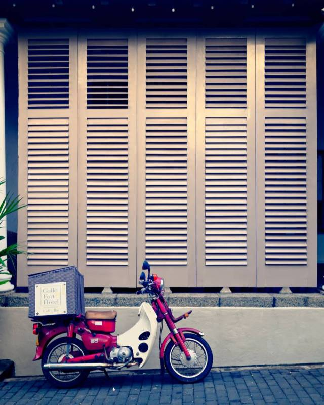 A red Honda Cub parked alongside the Galle Fort Hotel on Church Street