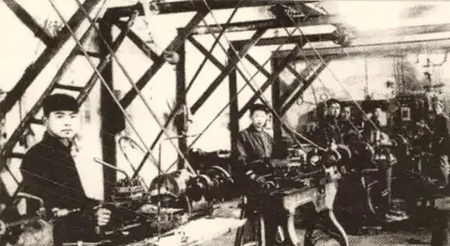 The workers in the picture are operating a belt lathe